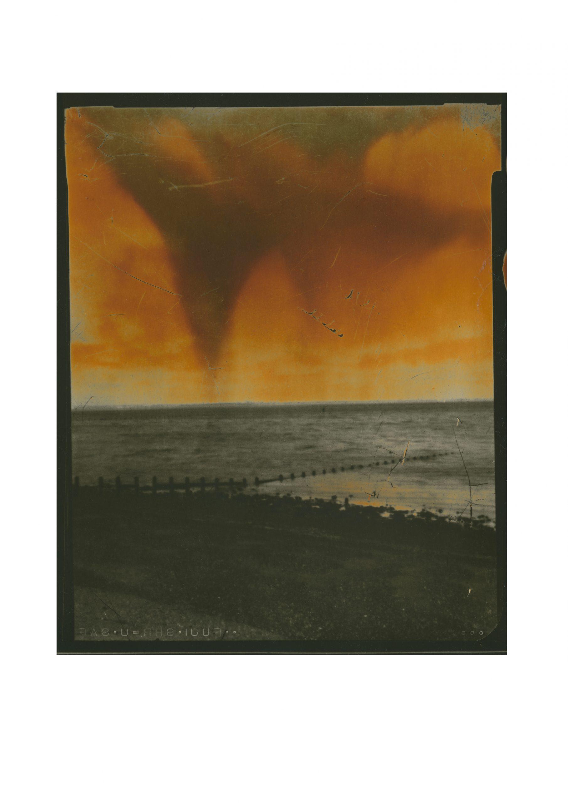 view of the sea lower half shingle and breakwaters top half painted acid orange dramatic sky
