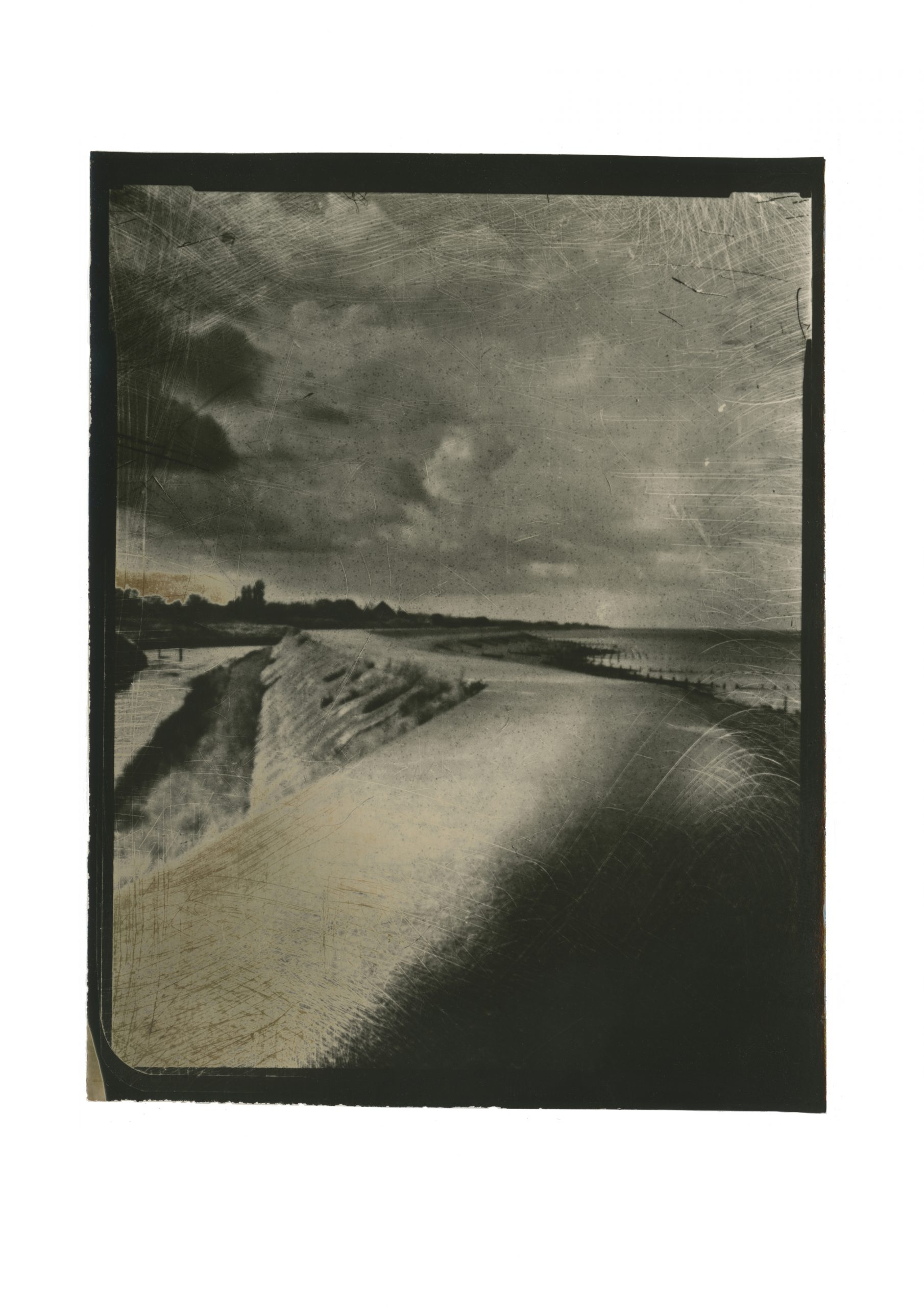 Sea defence straddled by two bodies of water, one on the left sea on the right.raised pathway  leading to a vanishing point with silhouettes of military buildings in the distance