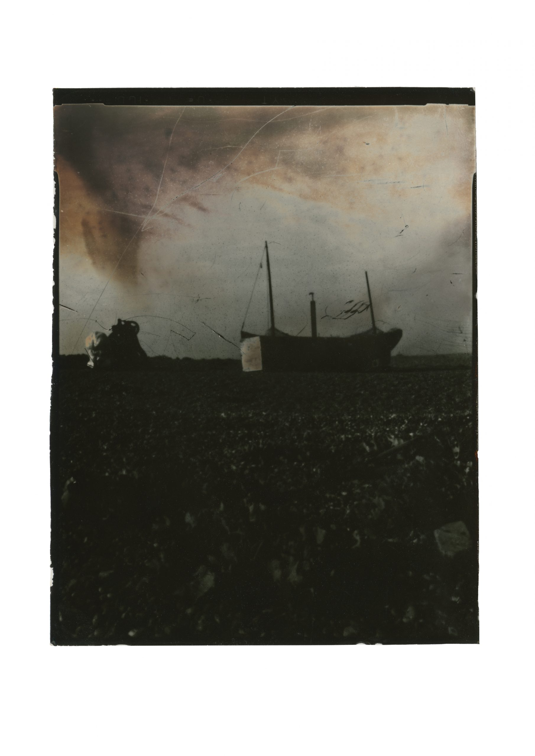 old fishing boat on horizon line as an almost silhouette lower half of the image dark shingle sky is like rusted metal with sweeping lines