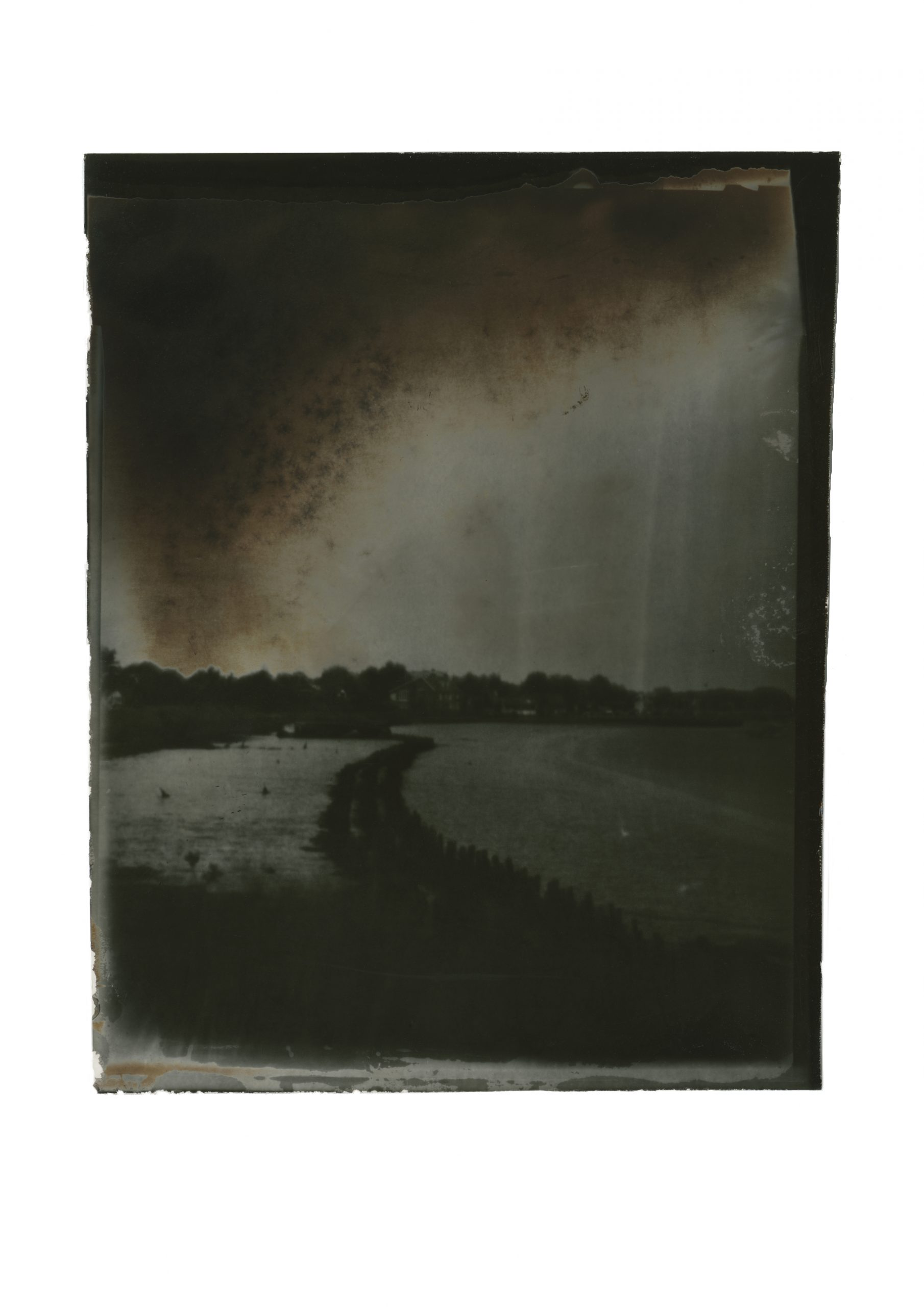 very dark sweeping sky, hints of orange against a steely grey. a coastal path straddled by two bodies of dark water leading to town on the horizon