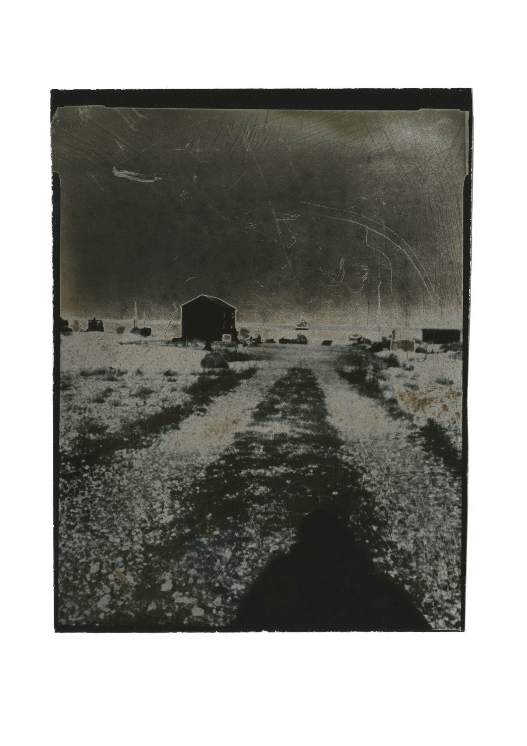 one point perspective path leading to horizon line with small huts in silhouette, shadow of figure in the foreground