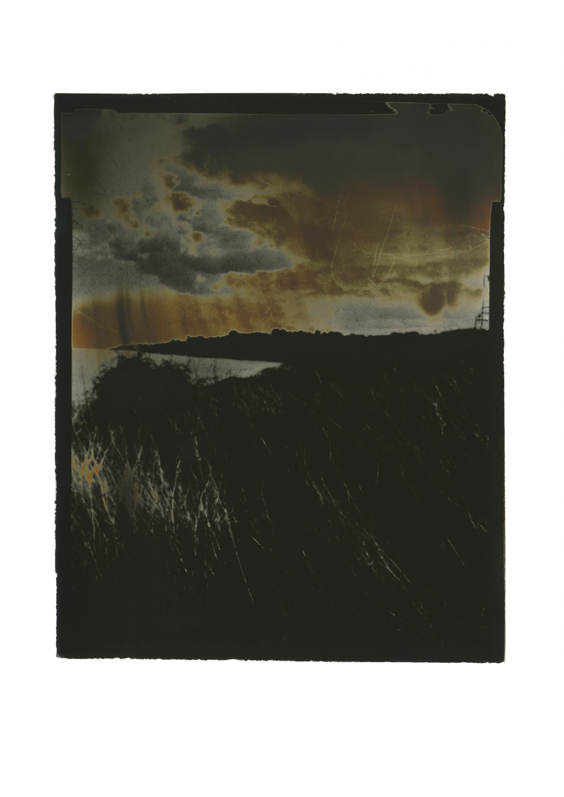very dark image of coastal headland on the left highlight of grasses orange sky with brooding clouds
