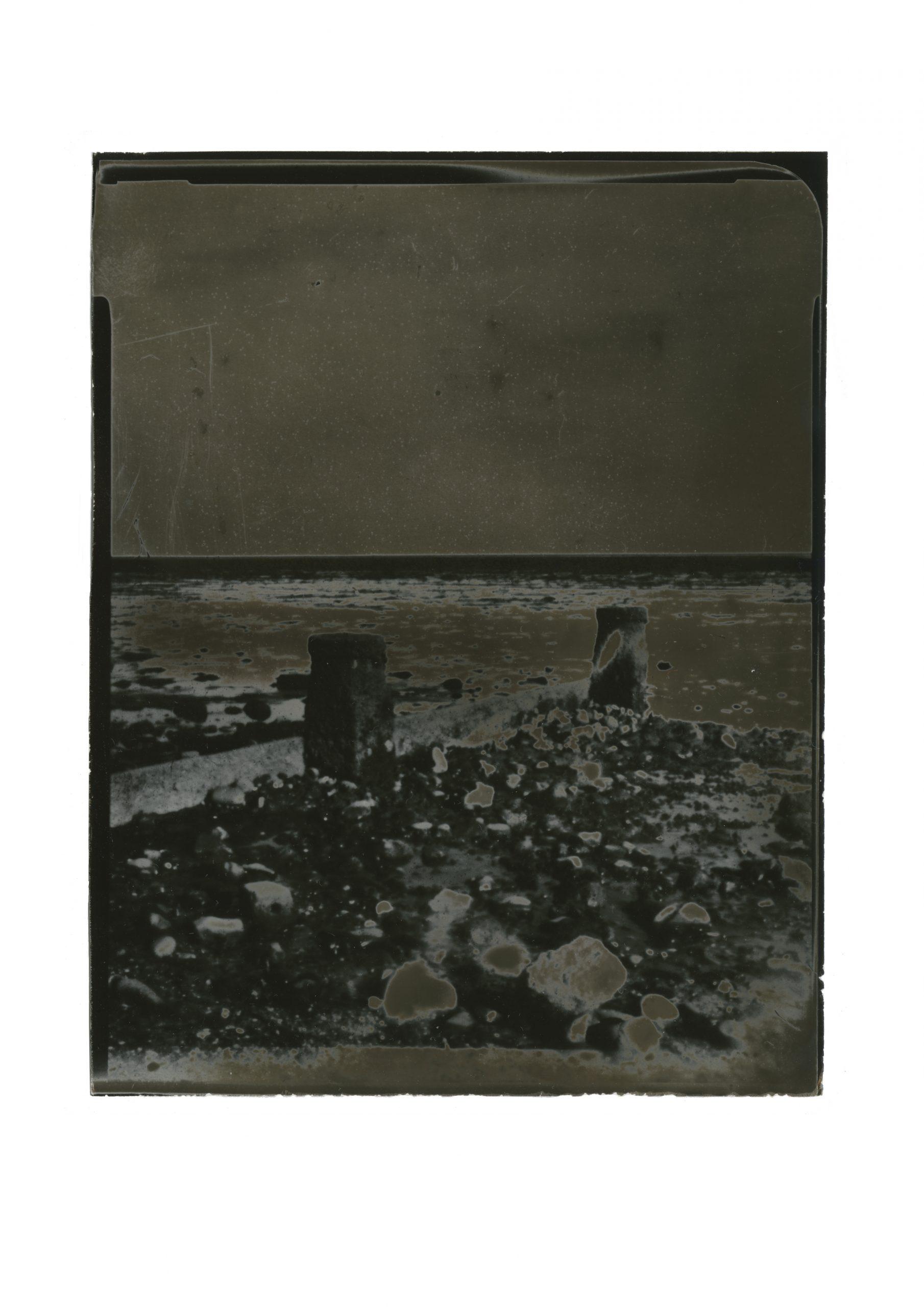 Dark solarized image of shingle beach, breakwaters and low tide against dark flat sky