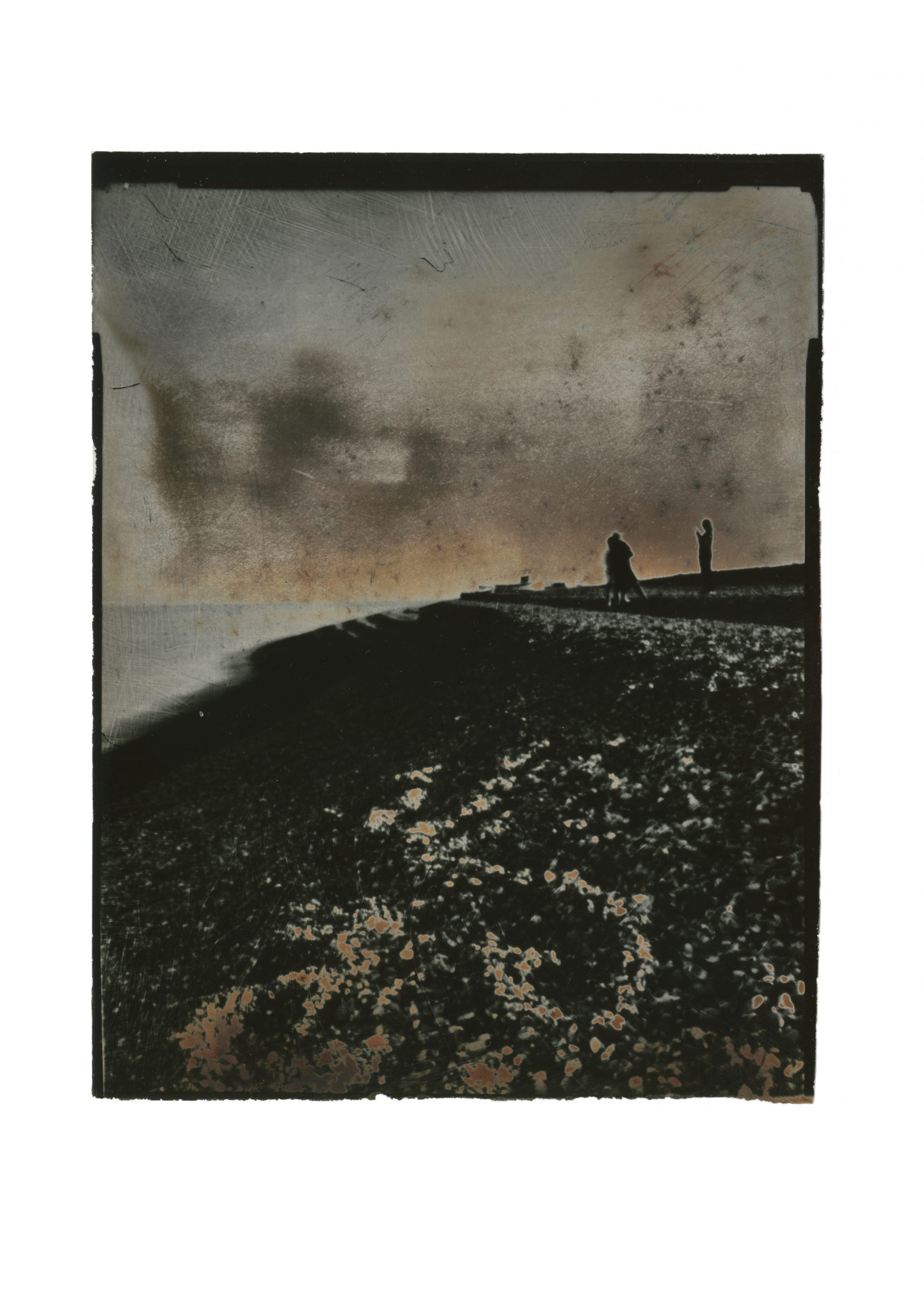 brooding contrasty image of steep bank of shingle with handprinted sky horizon line punctuated by shout of two figures